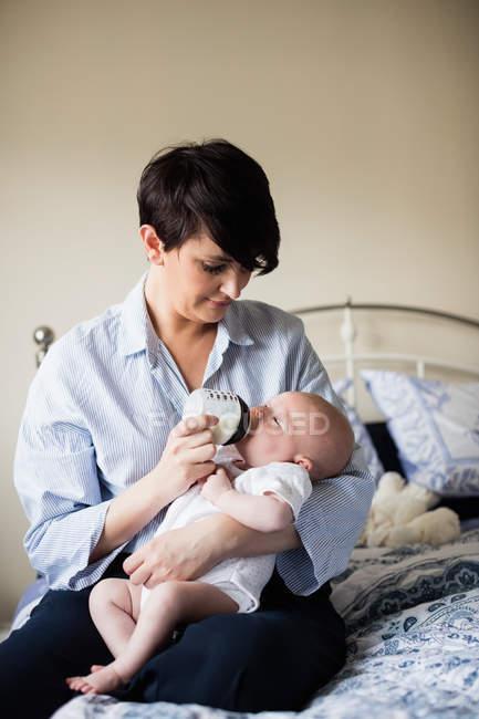 Madre alimentando al bebé con biberón en el dormitorio en casa - foto de stock