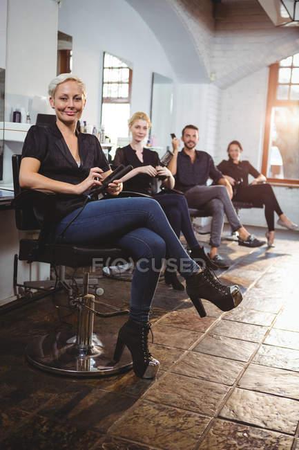 Portrait de coiffeurs souriants assis sur des chaises dans le salon — Photo de stock