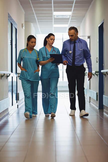Врачи и медсестры смотрят на планшет в коридоре больницы — стоковое фото