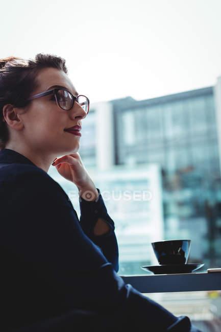 Junge Geschäftsfrau wegschauen im café — Stockfoto