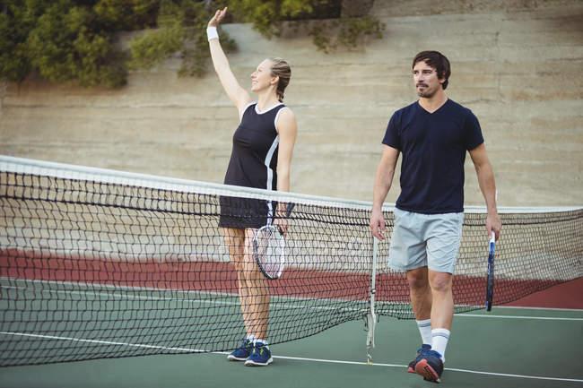 Jogadores de tênis andando e acenando em quadra esportiva após jogo — Fotografia de Stock