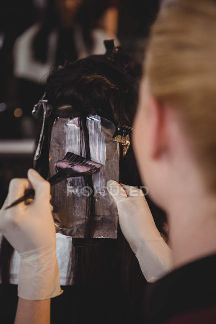Imagen recortada de peluquería teñir el pelo de su cliente en el salón - foto de stock
