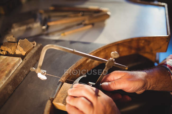Cropped image of goldsmith shaping metal with coping saw in workshop — Stock Photo