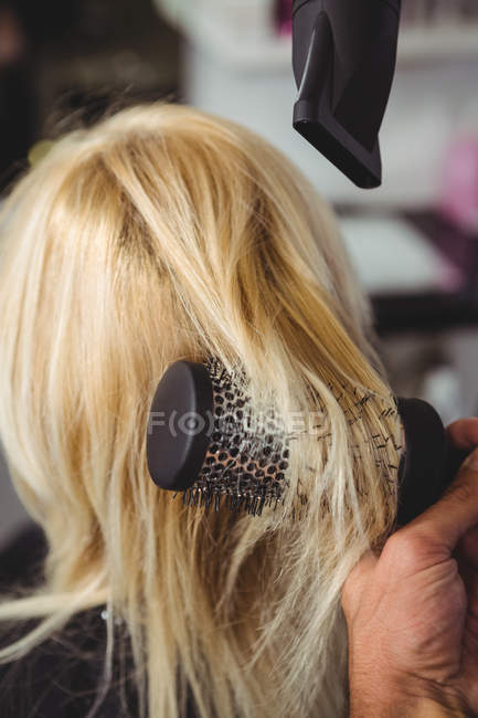 Cropped image of Woman getting her hair dried with hair dryer in hair salon — Stock Photo