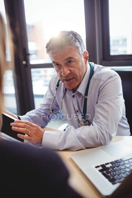 Médecin discutant avec le patient sur tablette numérique à l'hôpital — Photo de stock