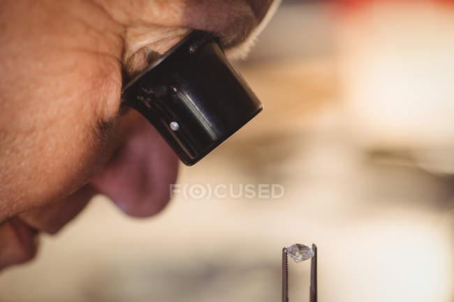 Goldsmith examining diamond through loupe in workshop — стоковое фото