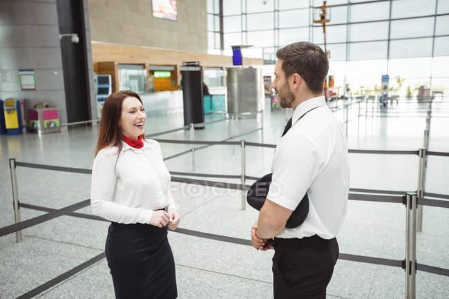 Piloto y azafata interactuando con otros en la terminal del aeropuerto - foto de stock