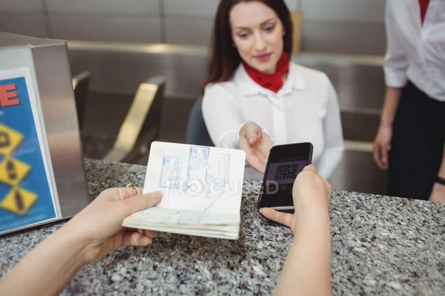 Dando um passaporte e um telefone móvel para um companhia aérea entrada atendente no balcão de check-in de passageiros — Fotografia de Stock