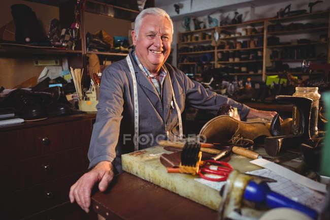 Ältester lächelnder Schuhmacher steht in Werkstatt — Stockfoto