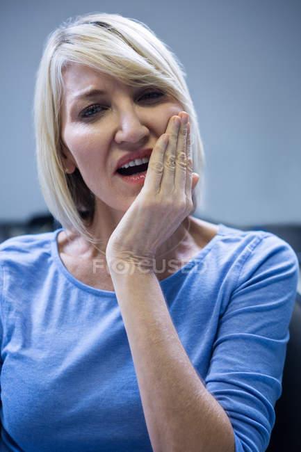 Ritratto di donna infelice con mal di denti in clinica dentale — Foto stock