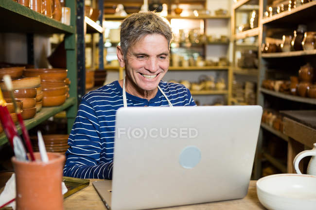 Happy male potter using laptop in pottery workshop — Stock Photo