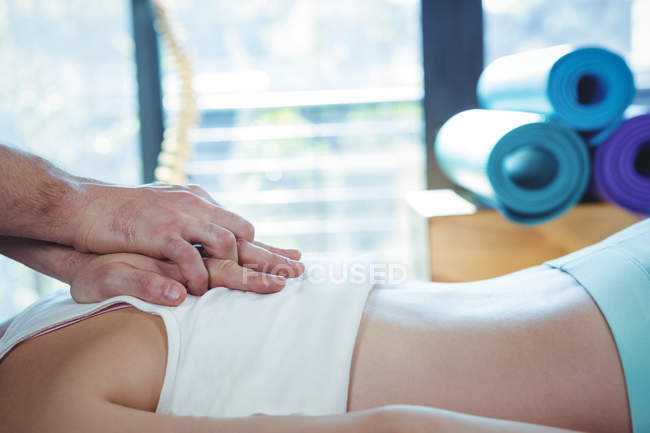 Обітнутого зображення чоловічого фізіотерапевт, віддаючи масаж пацієнтки в клініці — стокове фото