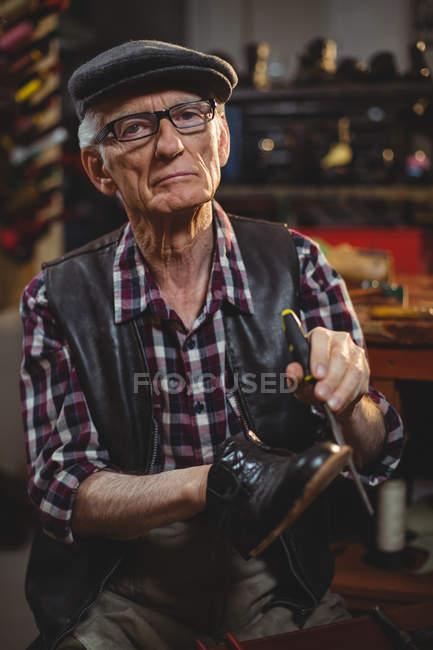 Sapateiro sênior reparando um sapato na oficina — Fotografia de Stock