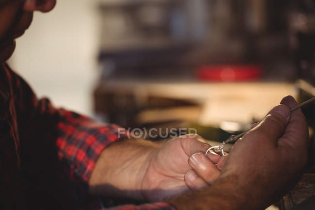 Гольфстрим закрепляет бриллиант на кольце с помощью пинцетов в мастерской — стоковое фото