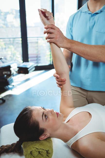 Чоловічий фізіотерапевта даючи arm масаж до жінки пацієнта в клініку — стокове фото