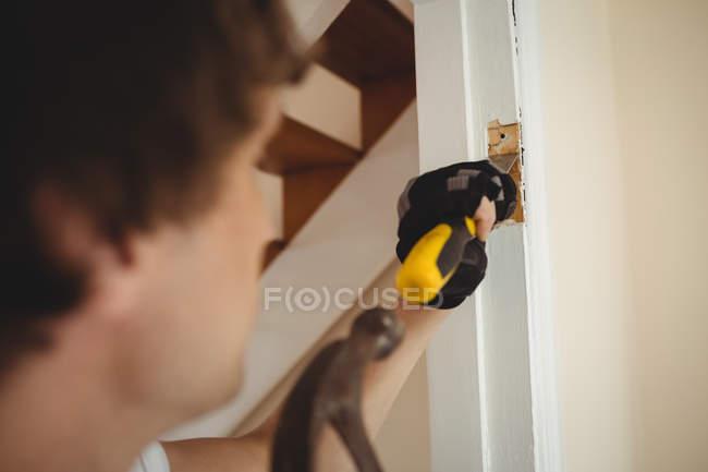 Carpintero trabajando en el marco de la puerta en casa - foto de stock