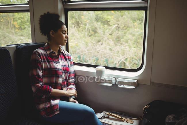 Молода жінка, що спить сидячи в поїзді — стокове фото