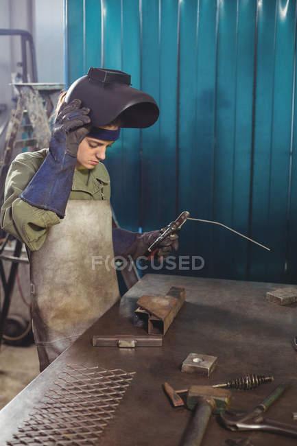 Female welder holding welding arch in workshop — Stock Photo