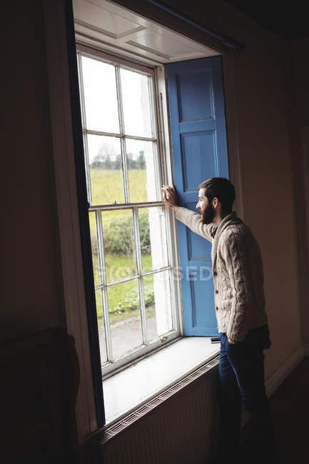 Uomo guardando attraverso la finestra a casa — Foto stock