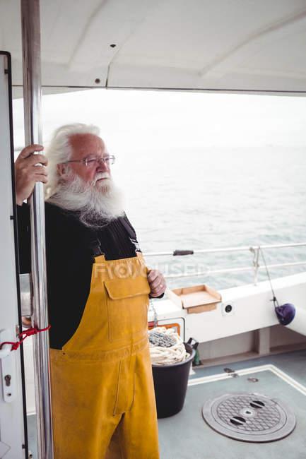 Nachdenklicher Fischer mit grauen Haaren steht auf Fischerboot — Stockfoto