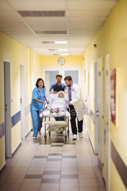 Arzt und Krankenschwester schieben Seniorin auf Trage in Krankenhausflur — Stockfoto