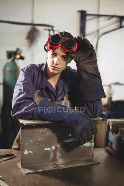 Porträt einer Schweißerin, die mit einem Metallstück in der Werkstatt steht — Stockfoto