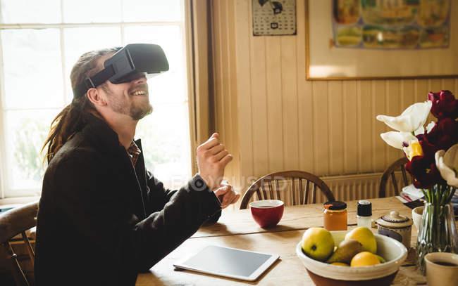 Happy hipster enjoying while using virtual reality simulator at home — Stock Photo