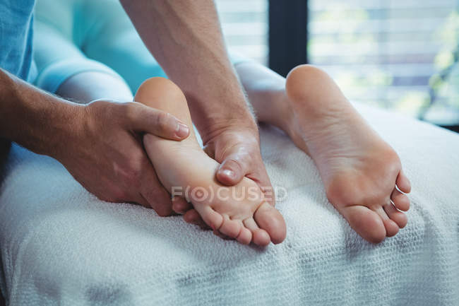 Imagen recortada de fisioterapeuta masculino dando masaje en los pies al paciente femenino - foto de stock
