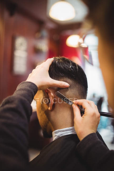 Man getting his hair trimmed with razor in barber shop — Stock Photo
