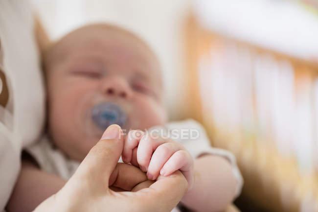 Imagen recortada de bebé sosteniendo la mano de la madre en casa - foto de stock