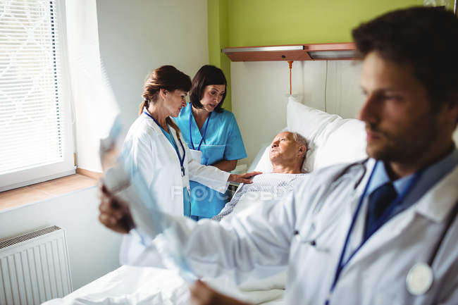 Female doctor consoling senior patient with nurse in hospital — Stock Photo