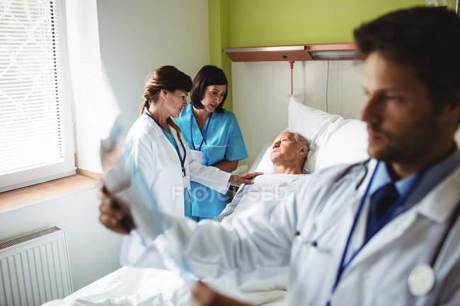 Жінка лікар, заспокоюючи старший пацієнта з медсестра в лікарні — стокове фото