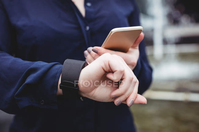 Midsection of buinesswoman using mobile phone — Stock Photo