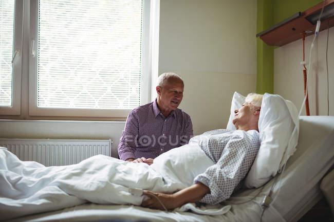 Hombre mayor consolando a mujer mayor en el hospital - foto de stock
