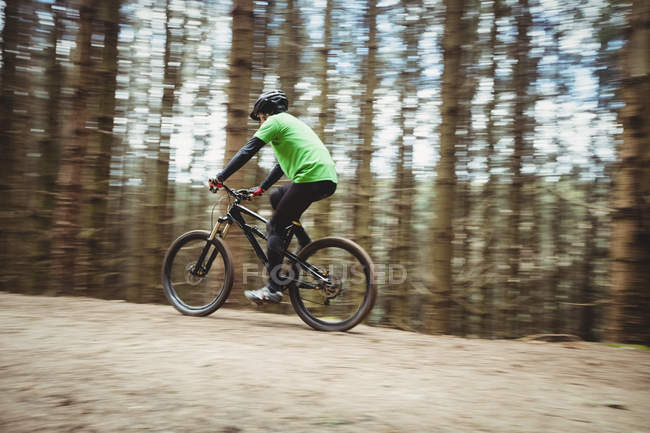 Вид сбоку на горного байкера, едущего по коварной дороге против деревьев в лесу — стоковое фото