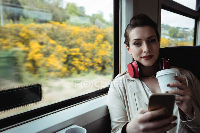 Portrait of woman using mobile phone while sitting in train — Stock Photo