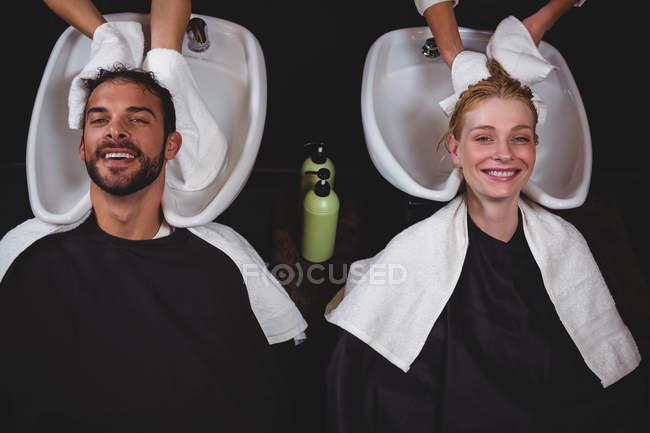 Estilistas de cabello seque el cabello clientes con toallas en el salón de - foto de stock