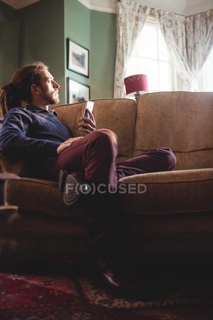 Volle Länge des nachdenklichen Hipster Mann mit Handy zu Hause auf sofa — Stockfoto