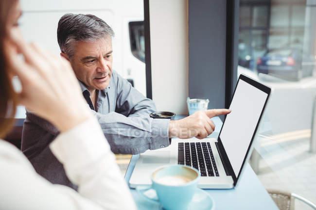 Uomo e donna discutono di laptop in mensa — Foto stock