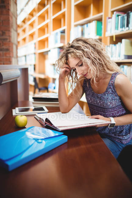 Woman sitting and reading book in library — Stock Photo
