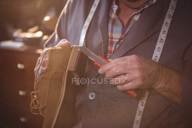 Mid section of shoemaker repairing a shoe in workshop — Stock Photo