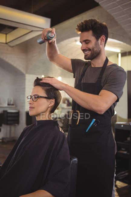 Sorridente parrucchiere maschile styling capelli dei clienti al salone — Foto stock