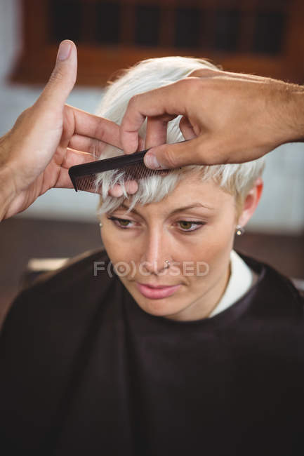 Female getting her hair trimmed at salon — Stock Photo