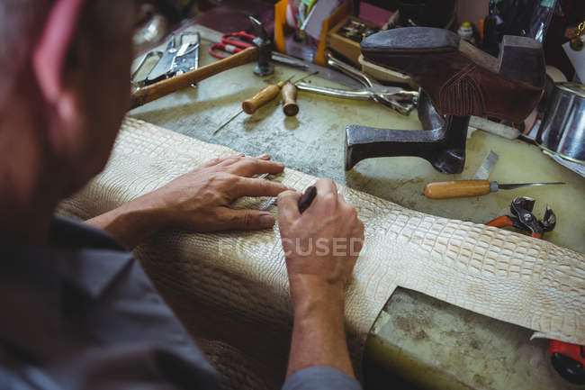 Shoemaker cutting a piece of material in workshop — Stockfoto