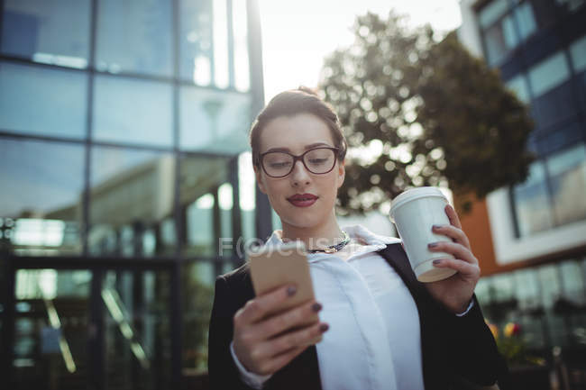 Businesswoman using mobile phone outside office building — Stock Photo