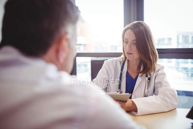 Врач сидит за столом, пишет на планшете перед пациентом в больнице — стоковое фото