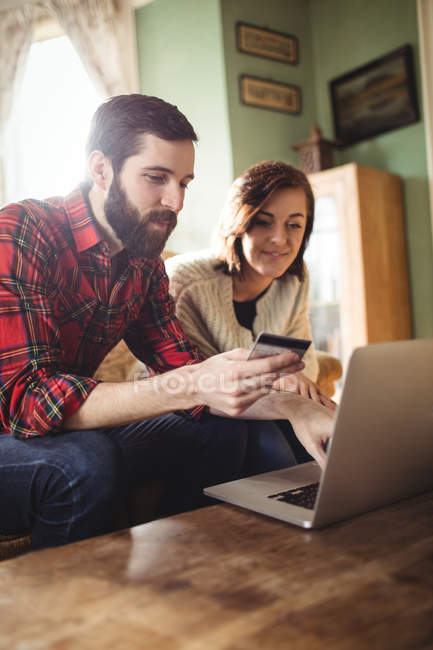 Couple shopping online on laptop in living room at home — Stock Photo