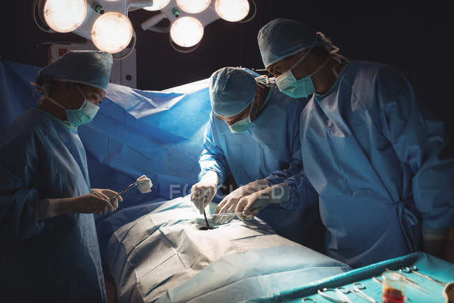 Team of surgeons performing operation in operation room at hospital — Stock Photo
