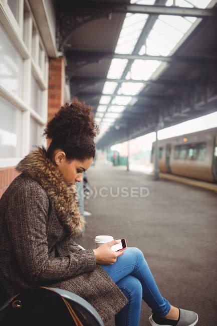 Женщина с телефоном, сидя на вокзале — стоковое фото