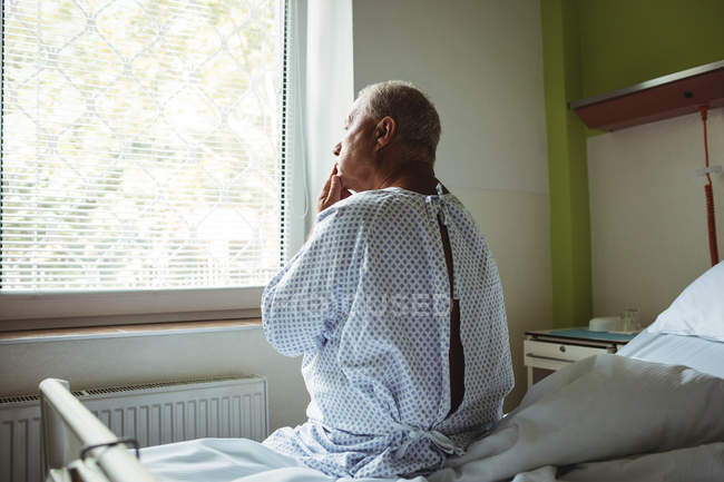Thoughtful senior man sitting on a bed at hospital — Stock Photo